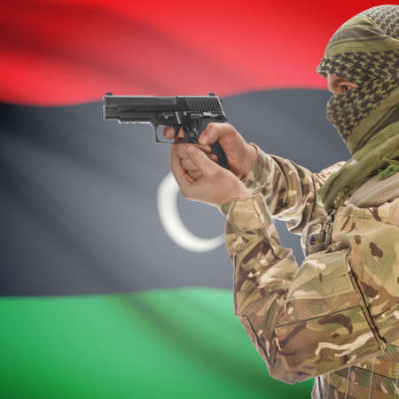 national police agency: Man with gun in hand and national flag on background series - Libya Stock Photo