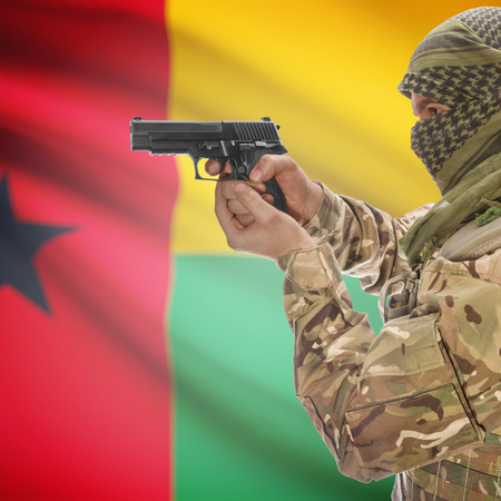 counterterrorism: Man with gun in hand and national flag on background series - Guinea-Bissau Stock Photo