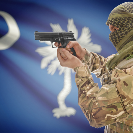 extremist: Male with gun in hand and American state flag on background series - South Carolina Stock Photo