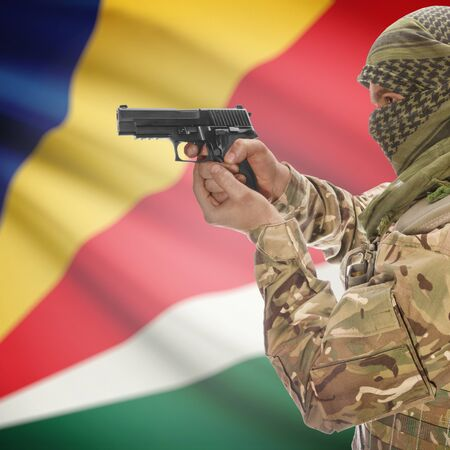national police agency: Man with gun in hand and national flag on background series - Seychelles