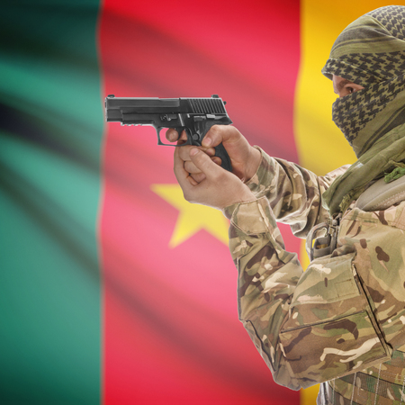 national police agency: Man with gun in hand and national flag on background series - Cameroon