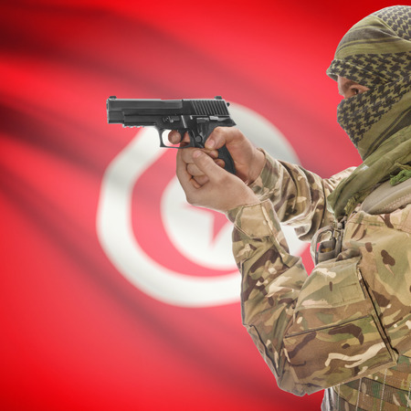 counter terrorism: Man with gun in hand and national flag on background series - Tunisia