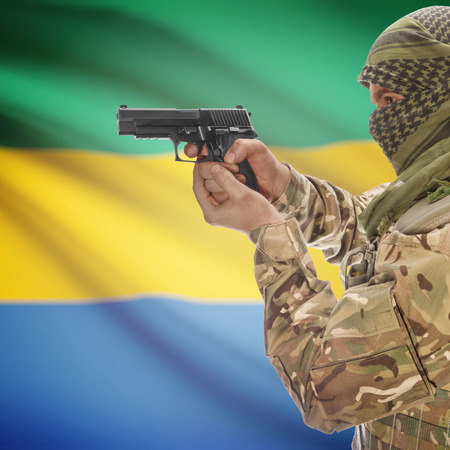 insurgency: Man with gun in hand and national flag on background series - Gabon Stock Photo