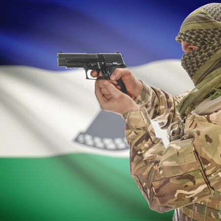 national police agency: Man with gun in hand and national flag on background series - Lesotho Stock Photo
