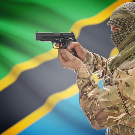 insurgency: Man with gun in hand and national flag on background series - Tanzania