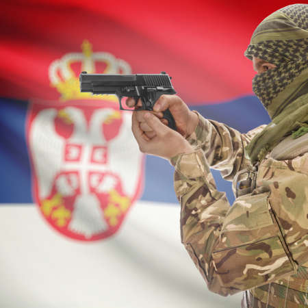 counterterrorism: Man with gun in hand and national flag on background series - Serbia