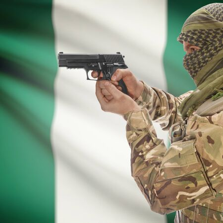 insurgency: Man with gun in hand and national flag on background series - Nigeria