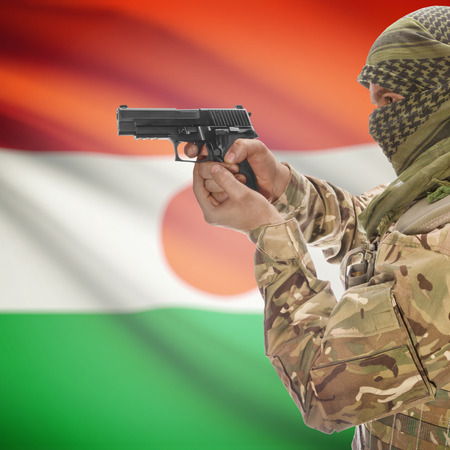 counterterrorism: Man with gun in hand and national flag on background series - Niger