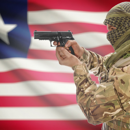 counterterrorism: Man with gun in hand and national flag on background series - Liberia