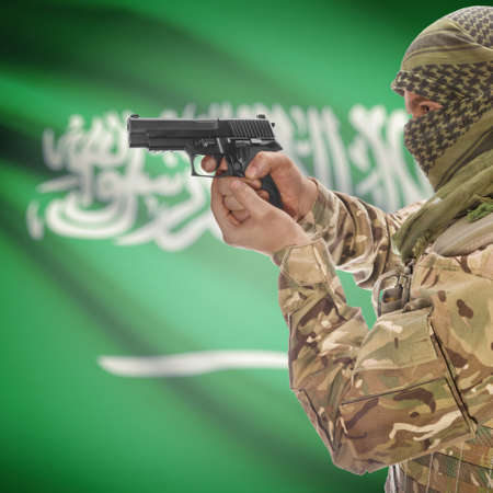 counterterrorism: Man with gun in hand and national flag on background series - Saudi Arabia