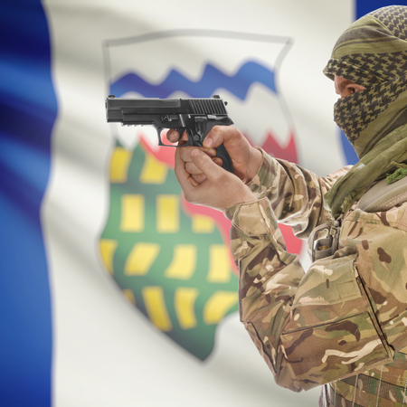 anti terrorist: Male with gun in hand and Canadian province flag on background series - Northwest Territories Stock Photo