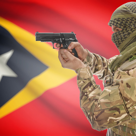 counterterrorism: Man with gun in hand and national flag on background series - East Timor