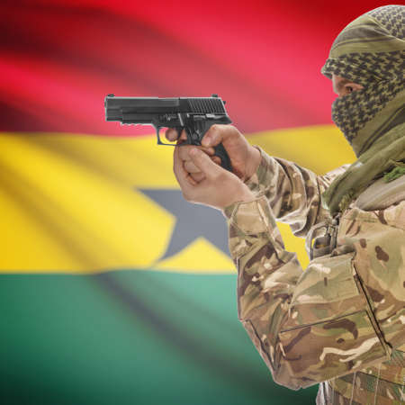 insurgency: Man with gun in hand and national flag on background series - Ghana