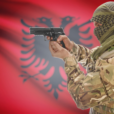 national police agency: Man with gun in hand and national flag on background series - Albania Stock Photo