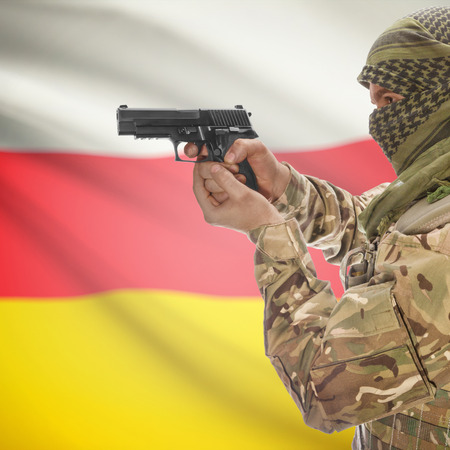 national police agency: Man with gun in hand and national flag on background series - South Ossetia Stock Photo