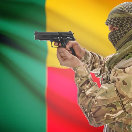 counterterrorism: Man with gun in hand and national flag on background series - Benin Stock Photo