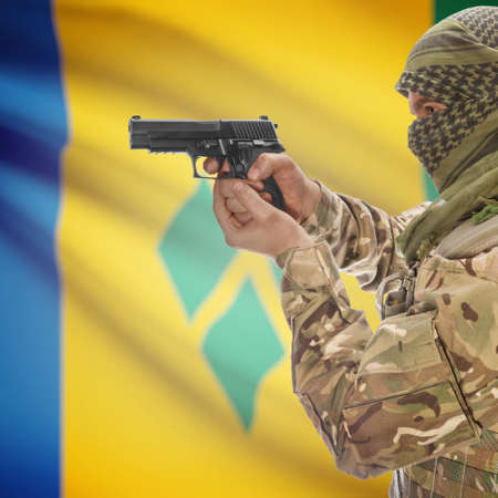 counterterrorism: Man with gun in hand and national flag on background series - Saint Vincent and the Grenadines Stock Photo