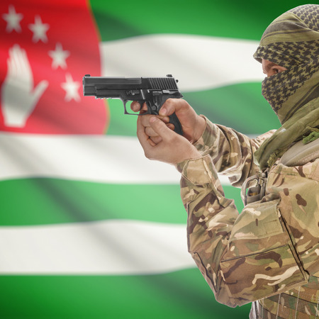 national police agency: Man with gun in hand and national flag on background series - Abkhazia Stock Photo