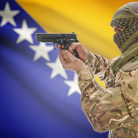counterterrorism: Man with gun in hand and national flag on background series - Bosnia and Herzegovina Stock Photo