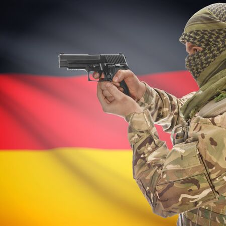 national police agency: Man with gun in hand and national flag on background series - Germany Stock Photo