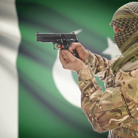 insurgency: Man with gun in hand and national flag on background series - Pakistan