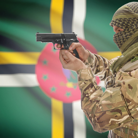 insurgency: Man with gun in hand and national flag on background series - Dominica Stock Photo