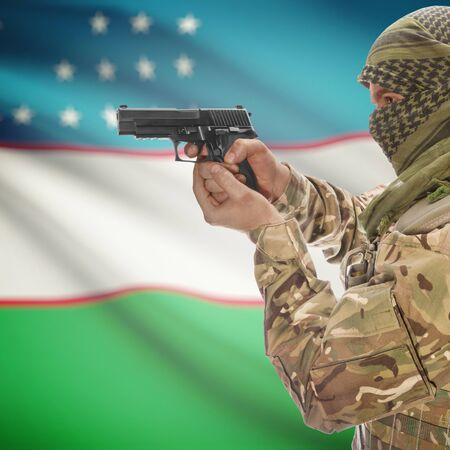 counterterrorism: Man with gun in hand and national flag on background series - Uzbekistan Stock Photo