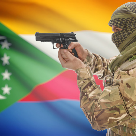 anti terrorist: Man with gun in hand and national flag on background series - Comoros