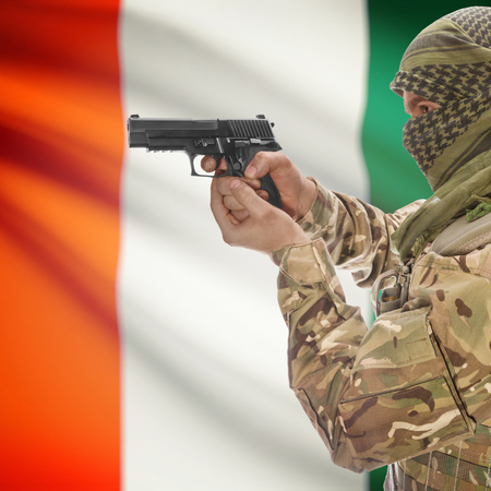 national police agency: Man with gun in hand and national flag on background series - Ivory Coast