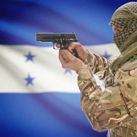 insurgency: Man with gun in hand and national flag on background series - Honduras Stock Photo