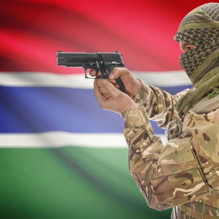 national police agency: Man with gun in hand and national flag on background series - Gambia