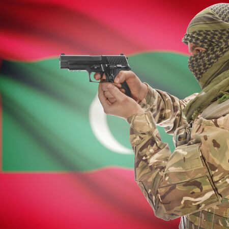 insurgency: Man with gun in hand and national flag on background series - Maldives
