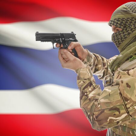 insurgency: Man with gun in hand and national flag on background series - Thailand Stock Photo