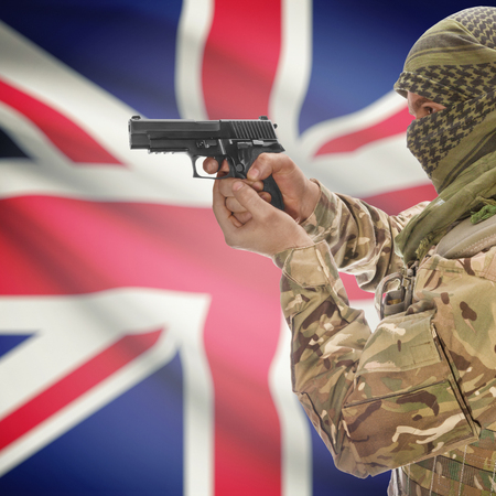 national police agency: Man with gun in hand and national flag on background series - United Kingdom Stock Photo