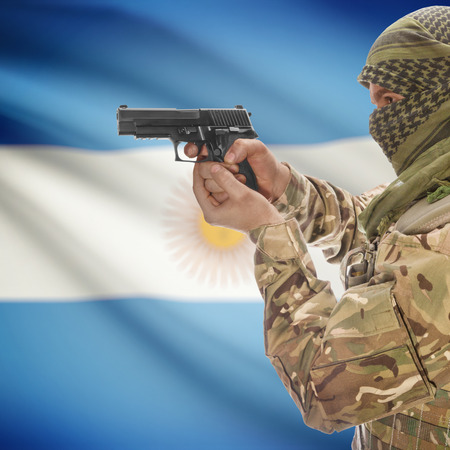 counterterrorism: Man with gun in hand and national flag on background series - Argentina