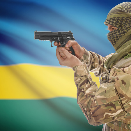counterterrorism: Man with gun in hand and national flag on background series - Rwanda Stock Photo