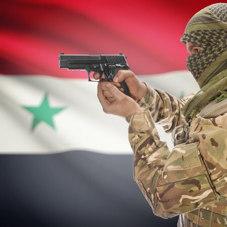 insurgency: Man with gun in hand and national flag on background series - Syria Stock Photo