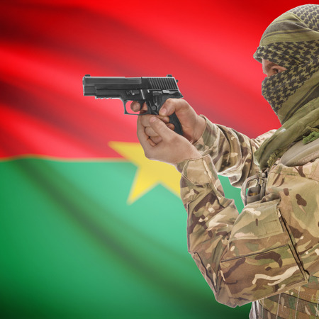 insurgency: Man with gun in hand and national flag on background series - Burkina Faso Stock Photo