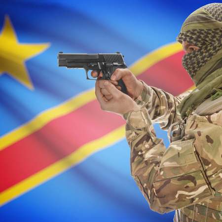 counterterrorism: Man with gun in hand and national flag on background series - Congo-Kinshasa Stock Photo