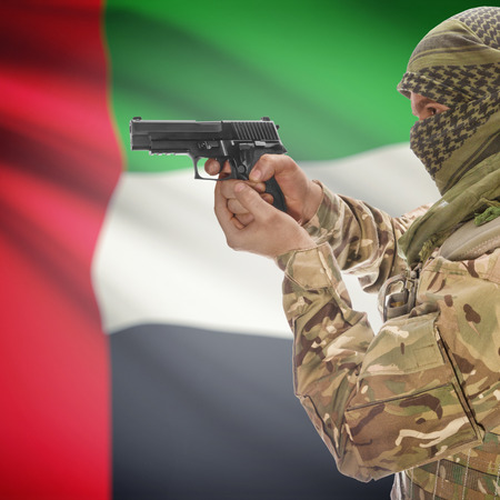 national police agency: Man with gun in hand and national flag on background series - United Arab Emirates