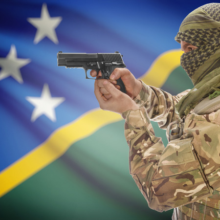 national police agency: Man with gun in hand and national flag on background series - Solomon Islands Stock Photo