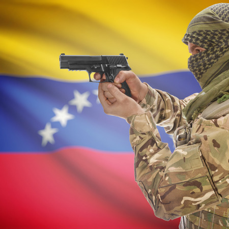 counterterrorism: Man with gun in hand and national flag on background series - Venezuela Stock Photo