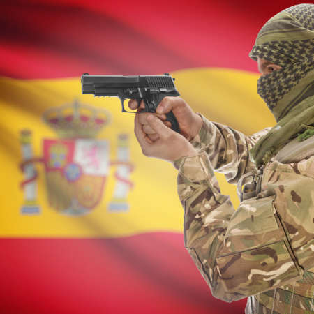 counterterrorism: Man with gun in hand and national flag on background series - Spain