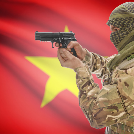 national police agency: Man with gun in hand and national flag on background series - Vietnam