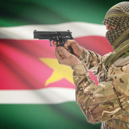 counterterrorism: Man with gun in hand and national flag on background series - Suriname Stock Photo