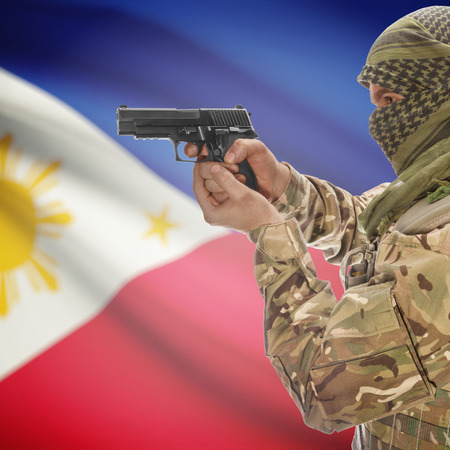 counterterrorism: Man with gun in hand and national flag on background series - Philippines