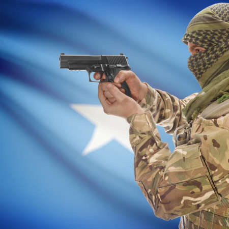 insurgency: Man with gun in hand and national flag on background series - Somalia