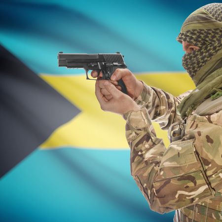 national police agency: Man with gun in hand and national flag on background series - Bahamas