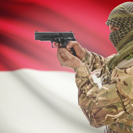 counterterrorism: Man with gun in hand and national flag on background series - Monaco Stock Photo