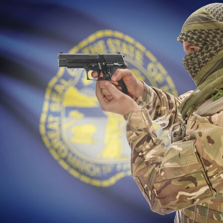 extremist: Male with gun in hand and American state flag on background series - Nebraska Stock Photo